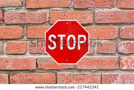 A bright red and white stop sign securely attached to a large old brick exterior wall. - stock photo