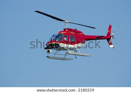 A bright red Bell 206 Jet Ranger helicopter with a camera on a Fleet Week Air Show in 2006. A little motion blur on rotor blades - stock photo