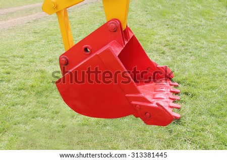 A Bright Red Bucket of a New Digger Excavator. - stock photo