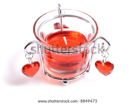 A bright red candle in glass with hearts
