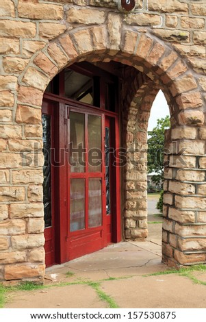 A bright red door and arched entry in an old sandstone building that was once a grocery store. - stock photo
