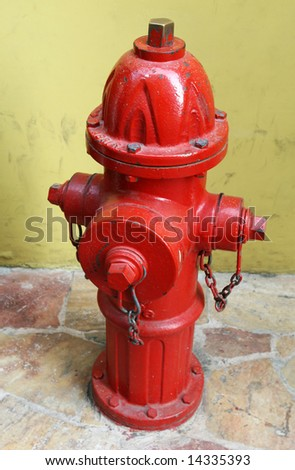 A bright red fire hydrant on a stone tiled sidewalk - stock photo