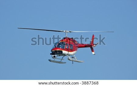 A bright red helicopter with a camera at a Fleet Week Air Show in 2006. A little motion blur on rotor blades - stock photo