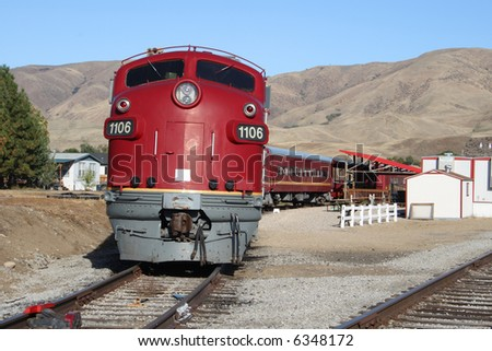 A bright red train sits on the tracks in southern Idaho, ready to go. - stock photo