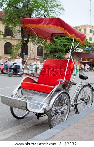 A bright red Vietnamese cyclo parked by road side with busy traffic - stock photo