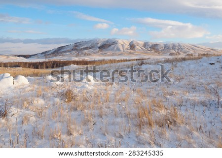 A bright view of sunlit hills in the Bannoye lake neighborhood after long-awaited snowfall, sunny winter day, South Urals, Russia. - stock photo