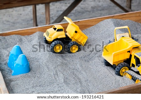 A bright yellow dump truck plastic toy in a raised wooden sand box with other plastic toys around it. - stock photo