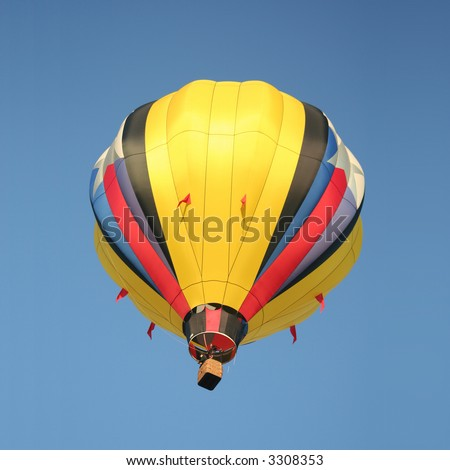 A Bright Yellow Hot Air Balloon Drifting Through a Clear Blue Sky - stock photo