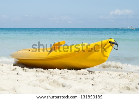 A bright yellow kayak on the beach - stock photo