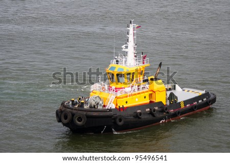 A bright yellow tug boat standing by to help ships in the harbor - stock photo