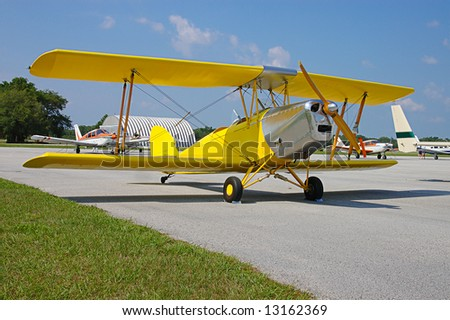 A bright yellow, vintage biplane parked on the tarmac at an air show with other planes in the background. - stock photo