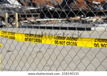 A bright yellow warning tape that reads Crime Scene Do Not Cross on a chain link fence - stock photo