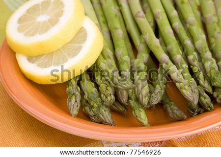 A brightly colored plate with asparagus spears and lemon slices. - stock photo