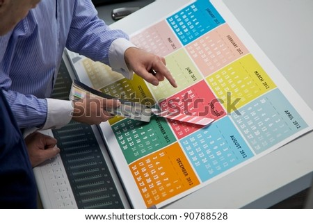 A brightly colored printed calendar being checked by a business man and a printing machine minder - stock photo