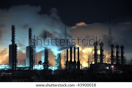 A brightly lit industrial site at night with plumes of smoke coming from chimneys.  Russia, Western Siberia. - stock photo