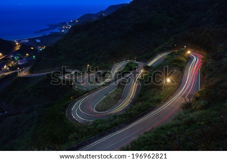 A brightly lit road twisting and curving up a mountain. - stock photo
