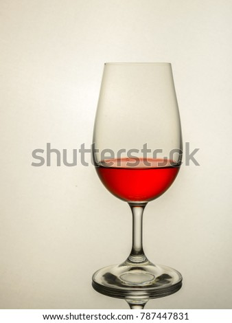A brightly lit wine glass with red wine on a reflective surface against a bright white background with clear space for overprinting text