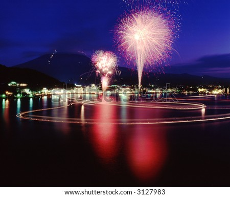 A brilliant display of Fireworks and their reflections in the water with Mount Fuji in the background - stock photo