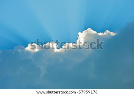 A brilliant, dramatic blue sky with clouds and sunbeams on a hot summer day. - stock photo