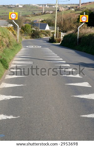 A British road with 30 miles per hour sign and warning markers on the road. - stock photo