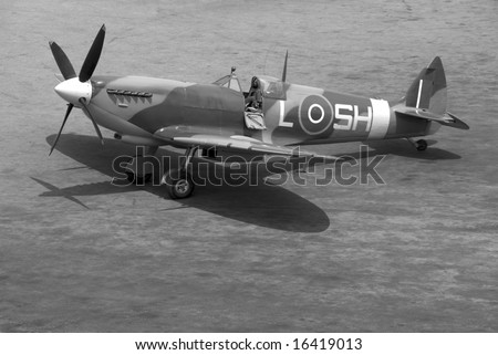 A British Spitfire fighter plane stands ready for action on an oil-stained airfield. - stock photo