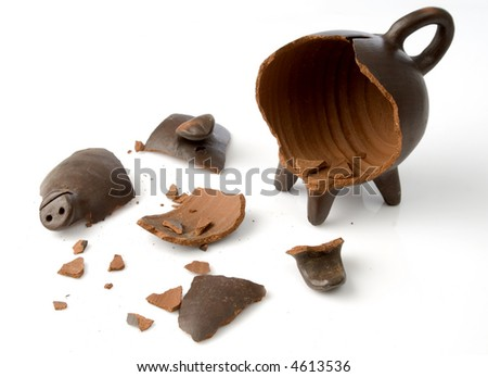 a broken and empty clay piggy money box over white background - stock photo
