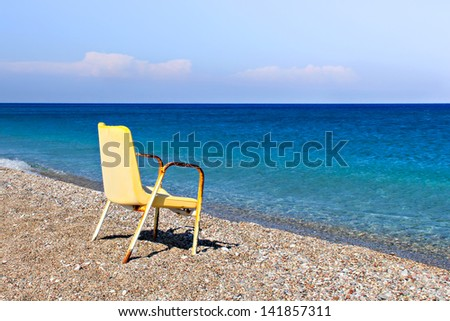 A broken and old chair at the greek beach. The concept of financial crisis