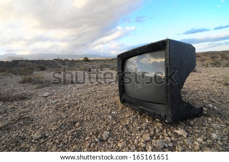 A Broken Black Television Abandoned in the Desert - stock photo