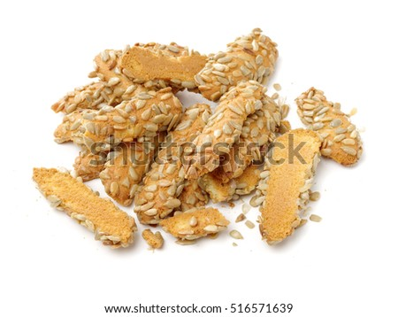 A broken breadstick with sunflower seeds and crumbs on white background