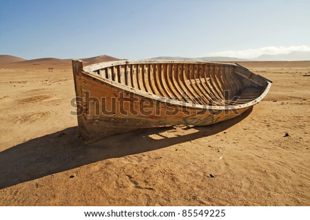 A broken, discarded boat in the desert - stock photo