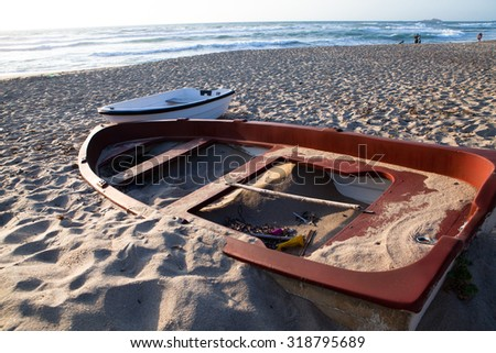 A broken, discarded boat on the seashore - stock photo