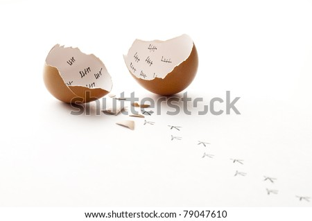 A broken egg and the chick footprints walking away - stock photo