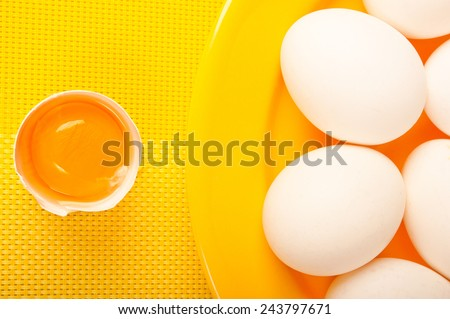 a broken egg with yolk with yellow plate and white eggs - stock photo