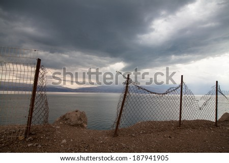 A broken fence at the dead sea coast - stock photo