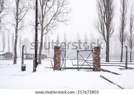 A broken gate in the snow covered concentration camp of Auschwitz  Birkenau, Poland - stock photo