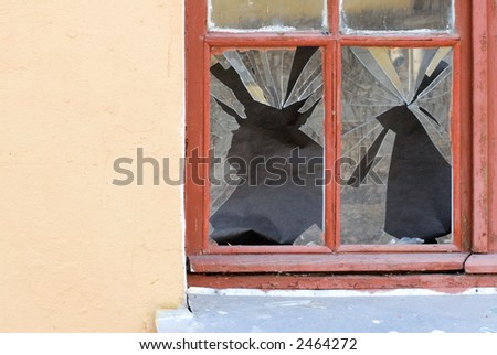 A broken glass window of abandoned house - stock photo