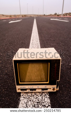 A Broken Gray Television Abandoned on the Road - stock photo