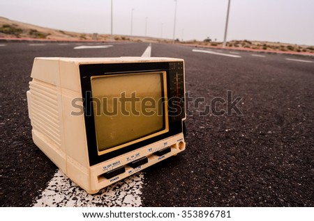 A Broken Gray Television Abandoned on the Road