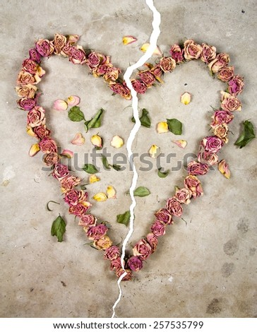 a broken heart made with old dried up flowers on a cold cracked concrete floor - stock photo