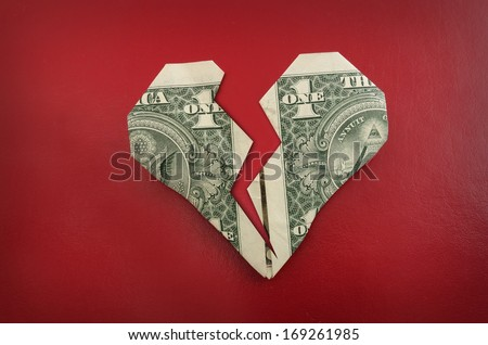 A broken origami dollar heart, on red                                - stock photo
