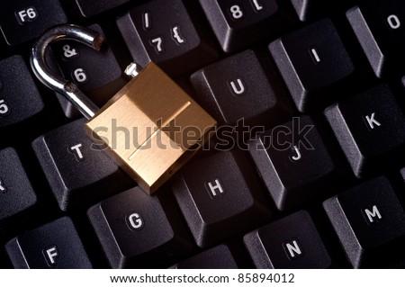 A broken padlock on top a computer keyboard to represent the concept of computer security breach - stock photo