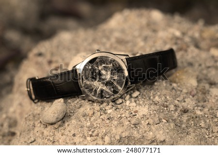 A Broken wristwatch on a pile of small stones. - stock photo