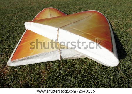 A Broken Yellow, Orange Surfboard On A Green Grass Field, Result Of Dangerous Surfing Conditions - stock photo