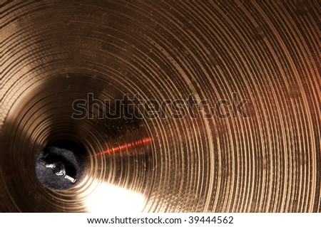 A bronze brass cymbal isolated close up in the horizontal format.