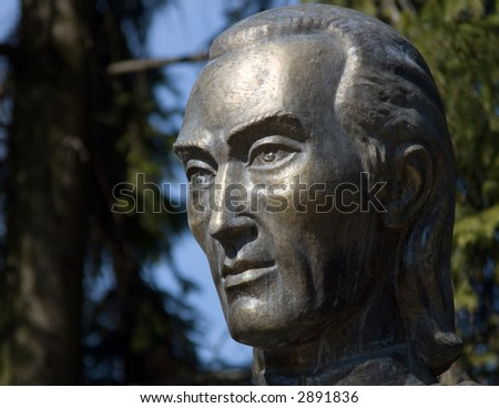 A bronze sculpture of a man's profile