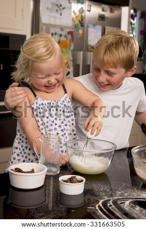 A brother and sister having fun whisking a cake mixture