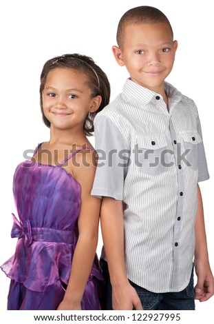 A brother and sister smile happily whilst standing close to each other. - stock photo