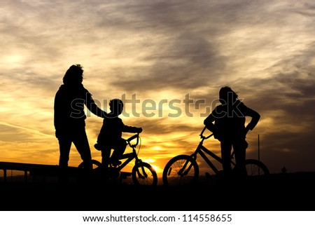 A brother and sister stand with their bikes along with their mother while watching the sunset.