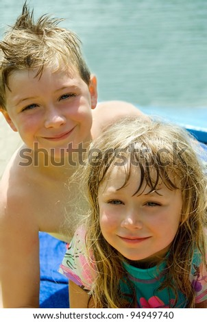 A brother and sister who are wet after a swim. - stock photo
