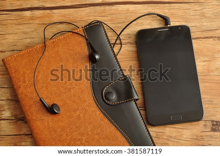 A brown and black leather note book displayed with a slim phone and earphones on a wooden background